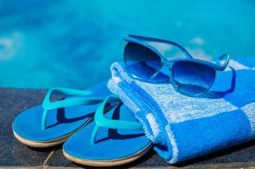 Blue slippers and sun glasses near swimming pool - holiday conce_198081